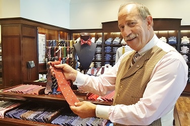 Associate Robert Rosenthal shows off a tie bearing the timeless Brooks Brothers company logo at the store at Bilmore Fashion Park. (Photo by Josh Coddington/Greater Phoenix Chamber of Commerce)